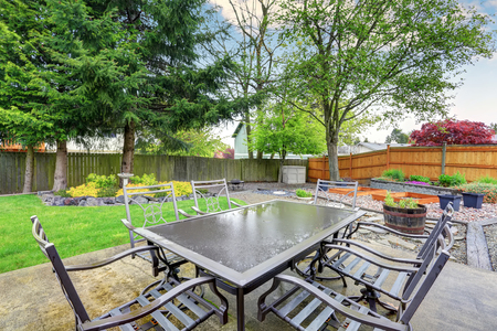Lovely patio with chair and table set, along with grass flled yard.