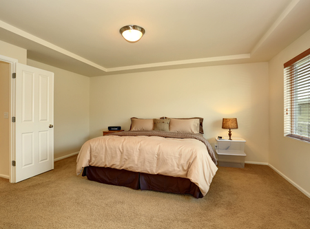 Simple master bedroom with TV and tan bedding. Stock Photo