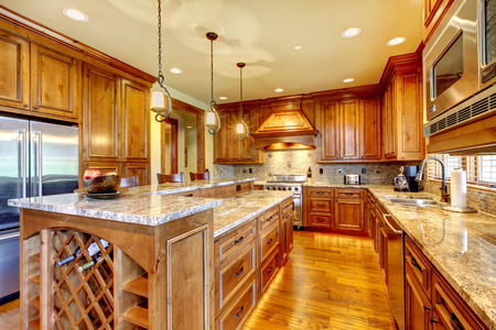 home appliance: Brilliant kitchen with stained wood cabinets, and glossy counter tops.