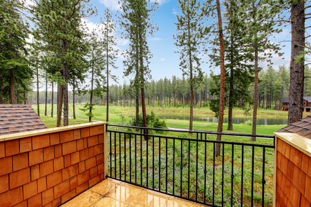 Beautiful view of small lake and greenery from deck of luxury home.