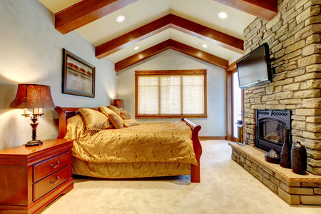 Elegant bedroom with golden bedding and a fireplace.