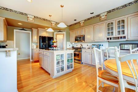 Moderní kuchyň s lesklou dřevěnou podlahu a novými spotřebiči.