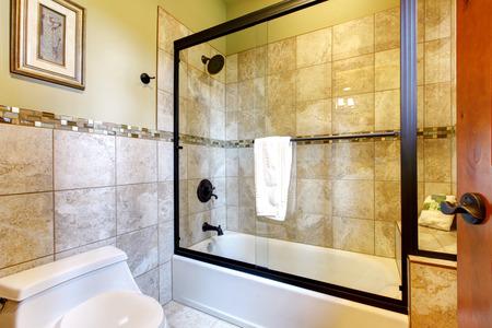 nice bathroom with tile floor and a glass shower door. Stock Photo