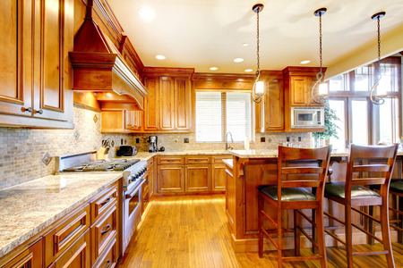 Brilliant kitchen with stained wood cabinets, and glossy counter tops.
