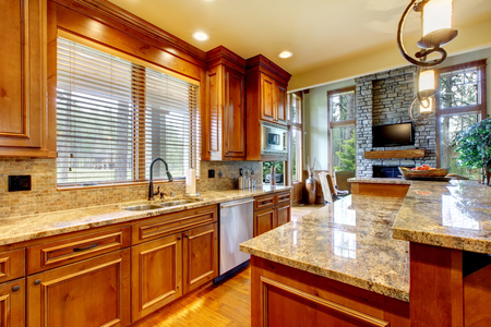 cabinets: Brilliant kitchen with stained wood cabinets, and glossy counter tops.