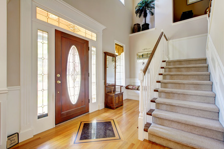 Nice entry way to home with carpet staircase and white interior.