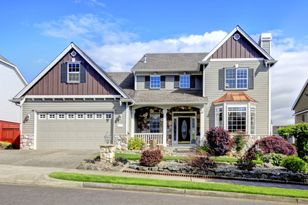 Modern house with navy blue door and perfect decorative front yard.