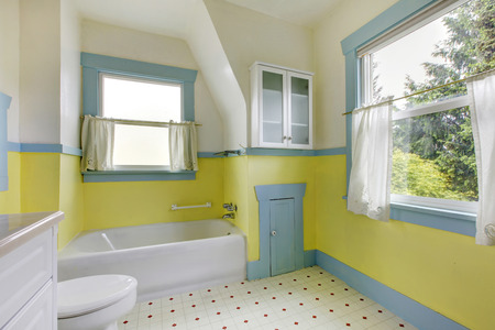 Cute bathroom with  yellow walls, and white accents.