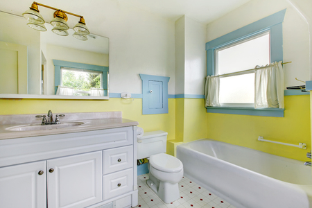 accents: Cute bathroom with  yellow walls, and white accents.