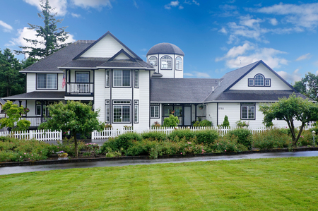 white trim: Large white house with blue trim and grass filled yard.