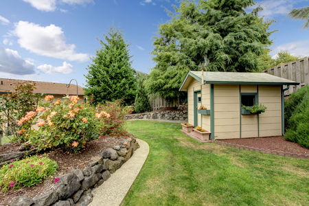 Achtertuin met groene huis shack, en tuin.