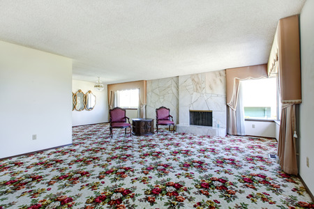 Large living room with two maroon chairs, and floral patterned carpet. Stock Photo