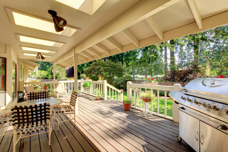 Long deck with grill, and a glass table.