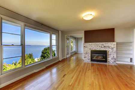 stone fireplace: Living room interior with hardwood floor, fireplace with natural stone tile and water view