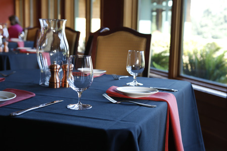 tablecloth: Table setting in  a restaurant with a blue tablecloth, red napkins and white plates