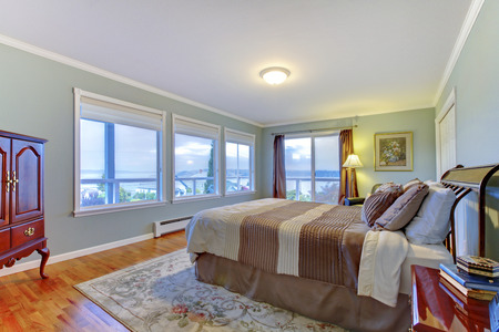 many windows: Luxury home master bedroom with many windows. blue walls, large brown bed and hardwood floor.