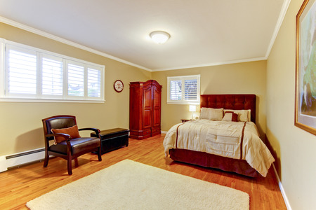 bedding indoors: Cozy large guest room with suede brown bed and armor, hardwood floors and beige walls.