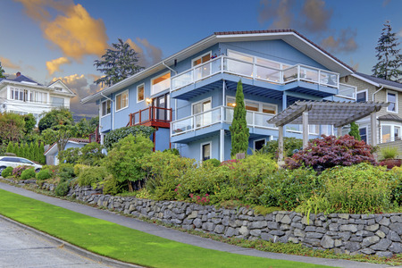 three story: Large three story tall blue house with summer landscape and rock wall. Stock Photo