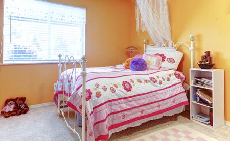 bed frame: Orange girl teenager kids bedroom with toys, white bed frame.