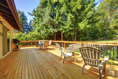 front  or back  yard: Large freshly painted new wooden deck with nice summer green backyard and outdoor furniture.