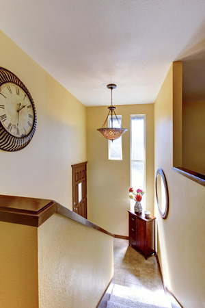 split level: House interior, yellow split level hallway entrance with front door and with clock.