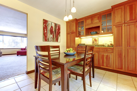 cabinets: Orange wood kitchen cabinets with dining room table with apples.