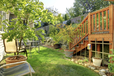 fenced: Small green fenced back yard with garden and shed