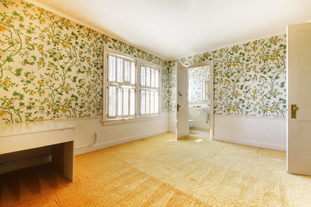 Adorable light bedroom with floral patterned wall paper and carpet connected with bathroom. Stok Fotoğraf