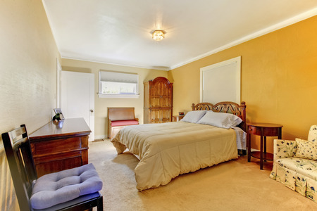 nightstand: Nice yellow bedroom interior with carved wood bed, nightstand and carpet.