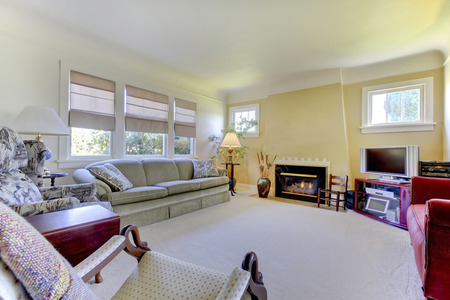 fireplace living room: Cozy living room with carpet floor, yellow walls and fireplace.
