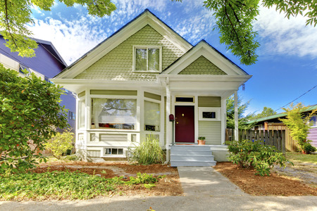 trimmed: Old small green home with porch and trimmed windows Stock Photo