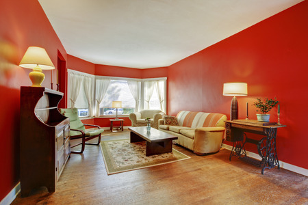 living room wall: Old country English living room interior with red walls, hardwood floor and rug Stock Photo