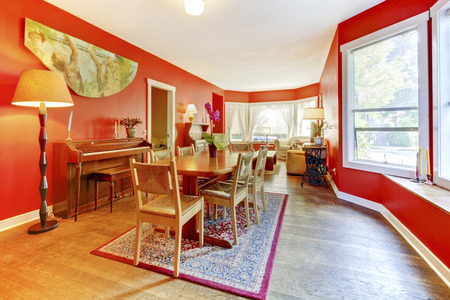 Red dining room interior with old wood piano and living room. area