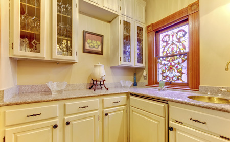kitchen cabinets: Kitchen area with marble top, cabinets and stained glass window. Stock Photo