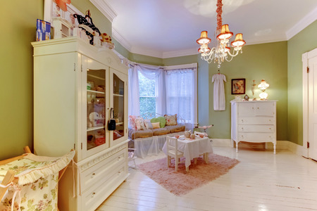 chandelier  kids: Cozy green girls room with white cabinets and pink rug.