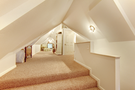 attic: Lovely beige attic bedroom with vaulted ceiling and carpet floor.