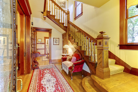 red sofa: Bright hallway with colourful rug, nice red sofa, wooden staircase and beige carpet covered steps.