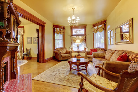 fireplace living room: Luxurious brown living room with fireplace, hardwood floor and mirror.