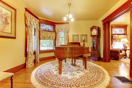 antique: Adorable vintage wood piano in luxurious living room interior with floral patterned curtains, carpet with oriental ornaments and antique carved wooden clock