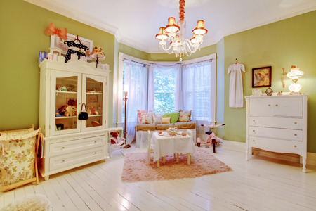 chandelier  kids: Adorable girls room with play area by the window.