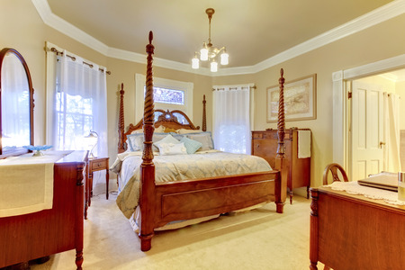 nightstand: Luxury beige and brown bedroom with high pole carved wood bed, nightstand and vanity cabinet. Stock Photo