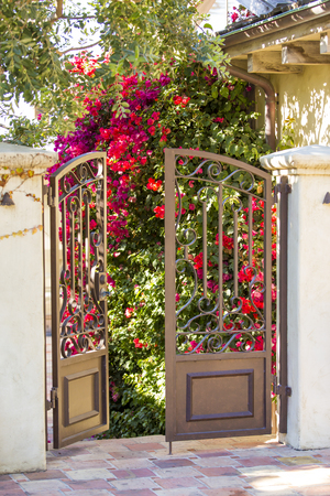 flowers garden: A partially open gate, entrance to a garden Stock Photo