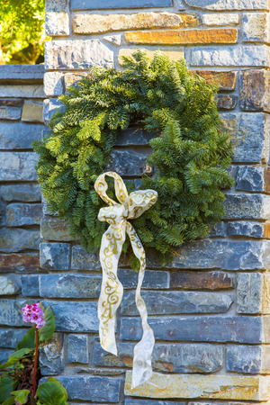 fense: Festive Christmas Advent wreath is hanging outside at stone fense background