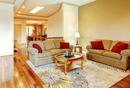 living room wall: Bright brown and red living room interior with hardwood floor, nice carpet and wooden  coffee table. View of hallway with staircase. Stock Photo