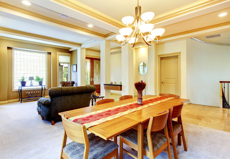 Cozy bright dining room connected with nicely furnished living room. View of entrance door. Stock Photo