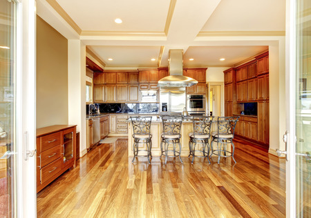 Modern wooden kitchen room design with hardwood floor, kitchen island, metal bar stools, trimmed ceiling and green walls. Stock Photo