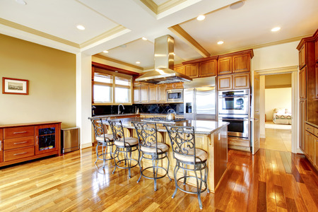 Modern wooden kitchen room design with hardwood floor, kitchen island, metal stools, trimmed ceiling and view of the living room.