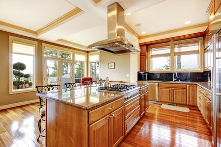 Modern wooden kitchen room design with hardwood floor, island, hood, granite counter top and view of the backyard.
