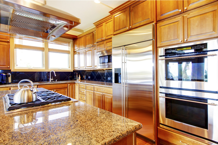 kitchen cabinets: Modern kitchen room interior with wooden cabinets, granite counter top, kitchen island and stainless steel refrigerator.