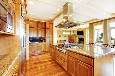 Modern wooden kitchen room with hardwood floor, island, granite counter top and view of the living room with fireplace.